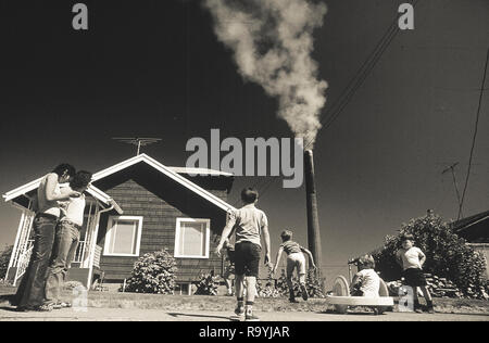 Smoke billows from industrial smokestacks in America as a family with children play nearby - Stock Photo