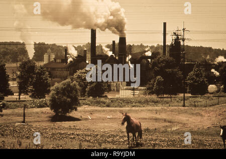 Smoke billows from industrial smokestacks in America affecting life - Stock Photo