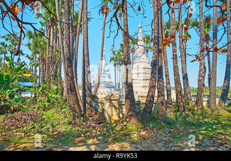 Walk in garden of old Bagaya Monastery with a view on carved stupas, decorated with fine patterns and sculptures, Ava (Inwa), Myanmar. - Stock Photo