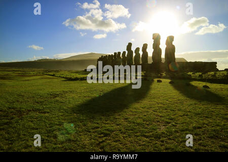 Silhouette of Moai statues against dazzling sunrise sky at Ahu Tongariki, the largest celemonial platform on Easter Island, Chile, South America - Stock Photo