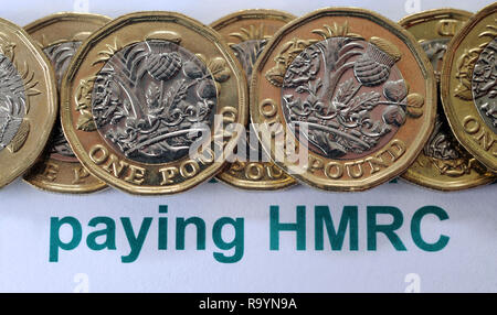 BRITISH ONE POUND COINS WITH HMRC LITERATURE RE PAYING PAYMENTS HER MAJESTYS REVENUE AND CUSTOMS TAX ETC - Stock Photo