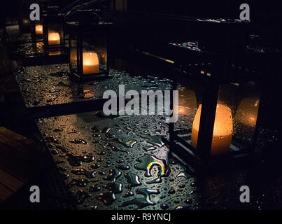 Candle lamps outside on the table in a line while it rains and the water reflects the light - Stock Photo