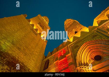 The beautiful carved stone minarets of Qalawun Complex in bright evening illumination, Cairo, Egypt - Stock Photo