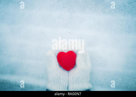 Red heart in woman's hands wearing white woolen mittens. Valentine's Day concept