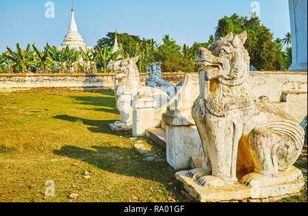 The old carved statues of chinthe - mythical Burmese leoryphs guard Desada Taya temple, the white pagoda of the complex is seen behind banana garden o - Stock Photo
