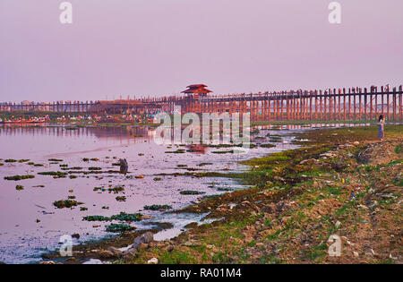 The old U Bein Bridge and silted bank of Taungthaman Lake are lighted in purple sunset colors, Amarapura, Myanmar. - Stock Photo