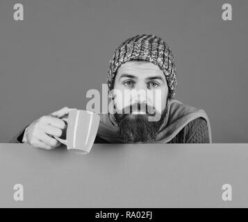 Fall season and influenza. Man with beard holds orange cup of medicine. Illness and autumn sickness concept. Guy with tired or depressed face wears warm hat on green and cyan background, copy space - Stock Photo