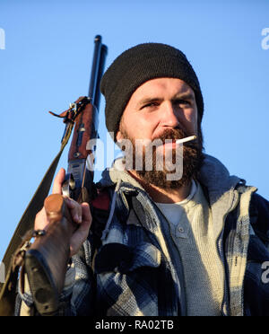 Hunter with rifle gun close up. Guy bearded hunter spend leisure hunting and smoking. Hunting masculine hobby concept. Man brutal bearded guy gamekeeper blue sky background. Brutality and masculinity. - Stock Photo