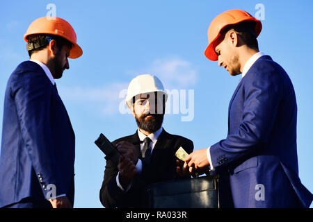 Board of architects with interested faces in suits and helmets take notes and hold money. Deal and construction concept. Builders make bargain. Workers and engineer hold meeting on blue sky background - Stock Photo