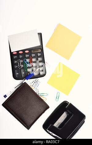 Office tools isolated on white background, close up. Business and work concept. Leather wallet and stationery. Calculator, hole punch, note paper, pen and paper clips. - Stock Photo