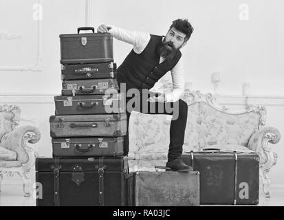 Man, butler with beard and mustache delivers luggage, luxury white interior background. Macho elegant on shocked face standing near pile of vintage suitcase. Luggage and travelling concept. - Stock Photo