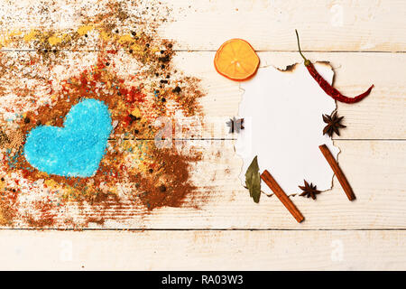 Food art concept. Set of spices on beige wooden background. Composition of condiment making heart shape filled with blue salt. Paper piece with cinnamon sticks, anise stars and dry orange slices. - Stock Photo