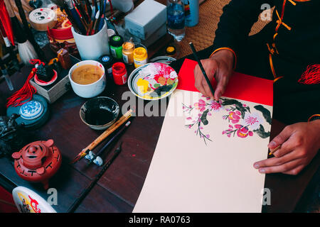 Vietnamese scholar writes calligraphy at lunar new year. Calligraphy festival is a popular tradition during Tet holiday. Culture of Vietnamese Tet - Stock Photo