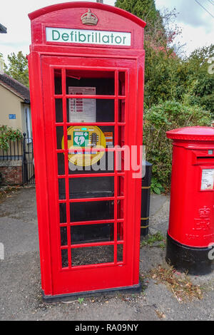 Castle Headingham, Essed, UK - October 26, 2018: Old red telephone box converted into village defibrillator for heart emergencies. - Stock Photo