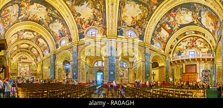 VALLETTA, MALTA - JUNE 18, 2018: Panorama of stunning interior of St John's Co-Cathedral with carved gilt patterns, frescoes, sculptures, scenic altar - Stock Photo