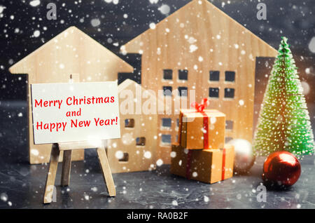 Christmas tree, wooden houses and gifts with the inscription 'Merry Christmas and Happy New Year!'. New Year card. Congratulations on a holiday from a - Stock Photo