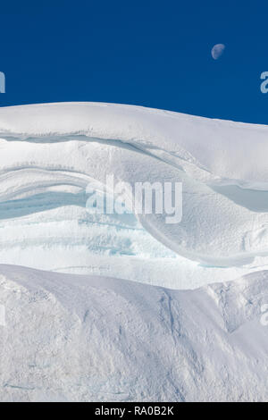 Antarctica, Antarctic peninsula, Gerlach Straight, Wilhelmina Bay in the Enterprise Island area. Moon over snowy mountain edge. - Stock Photo