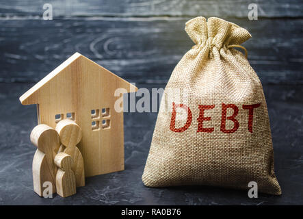 A bag of money with the word Debt and the family standing near the house. The concept of debt for housing. Mortgage. Real estate, home savings, loans  - Stock Photo
