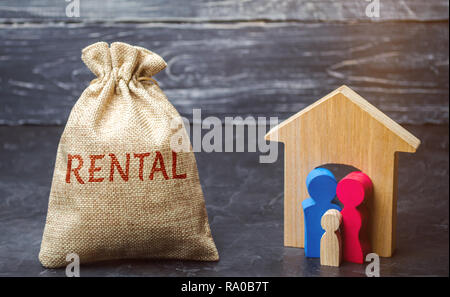 A bag with money and the word Rental and a family standing near the house. The accumulation of money to pay rental housing. Rental apartment. Saving m - Stock Photo