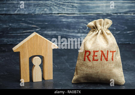 A bag with money and the word Rent and a house with a tenant inside. The accumulation of money to pay rental housing. Rental apartment. Saving money.  - Stock Photo
