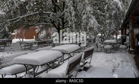 picnic tables covered with snow at empty cafe with red no entrance sign in background - Stock Photo