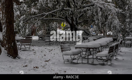 picnic tables covered in snow with yellow pedestrian sign in background - Stock Photo