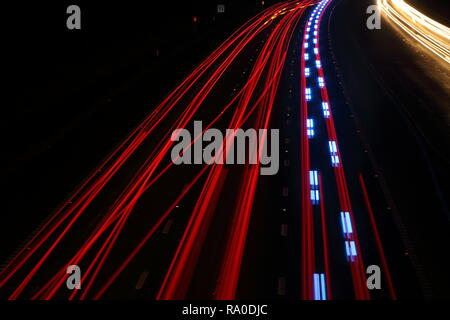 Traffic light trails with the blue of a police car - Stock Photo