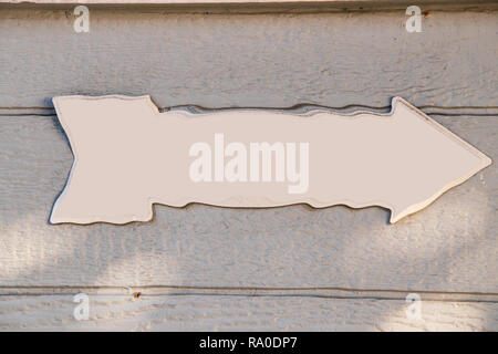 White arrow with distorted edges on a gray wooden background - Stock Photo