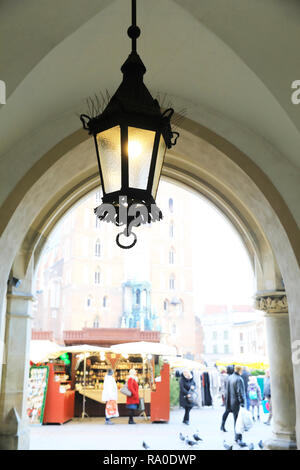 Looking out from the vaulted Cloth Hall onto the Christmas market in the Main Market Square in Krakow, Poland - Stock Photo