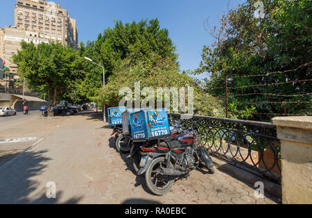 Fish Market restaurant food delivery motorbikes parked by the roadside on a sunny day in Giza, Cairo, Egypt - Stock Photo