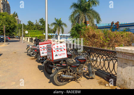TGI Fridays restaurant delivery motorbikes parked by the roadside on a sunny day in Giza, Cairo, Egypt - Stock Photo