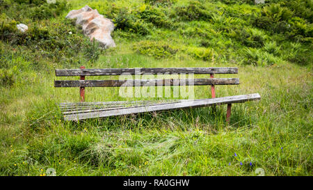Empty broken bench in midst of high wet grass near a hiking path in Tyrol, Austria - Stock Photo