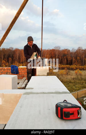 The masonry mooring the wall in the fresh air with a trowel and glue solution 2018 - Stock Photo