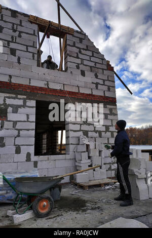 A worker using a hand winch raises a cement mortar bin on the second floor 2018 - Stock Photo