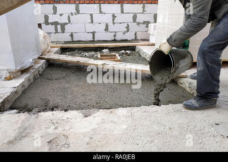 auxiliary worker pours out of a bucket liquid cement mortar on the floor between the floors of the house 2018 - Stock Photo
