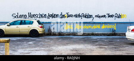 graffito on the wall of a building, text reads: _'as long as humans think that animals don`t feel, animals have to feel that humans don´t think' - Stock Photo