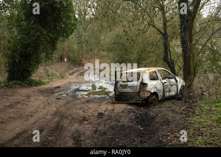 Burnt out stolen car in the UK countryside. - Stock Photo
