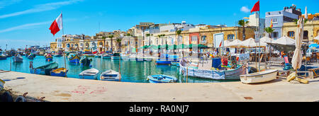 MARSAXLOKK, MALTA - JUNE 18, 2018: The harbour of the fishing village with many small luzzu boats is surrounded by traditional low houses of native li - Stock Photo