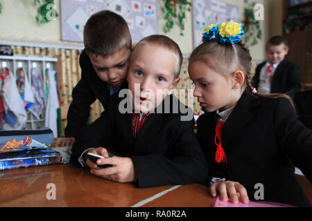 Ukrainian schoolchildren playing with the mobile.The school of Radinka is located near by the Chernobyl Exclusion Zone.The area is contaminated. - Stock Photo