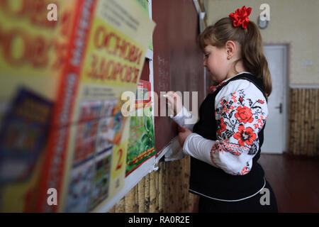 Ukrainian schoolgirl writes on the blackboard. The school of Radinka is nearby the Chernobyl Exclusion Zone, the area is radioactive contaminated. - Stock Photo