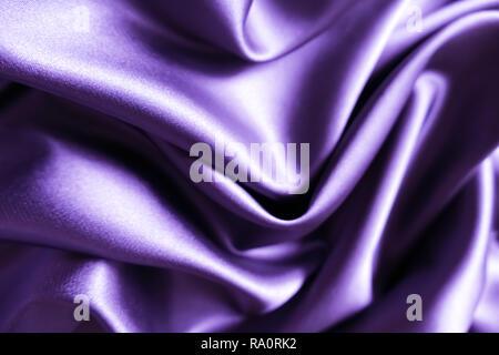 Smooth elegant wavy purple / violet satin silk luxury cloth fabric texture, abstract background design. - Stock Photo