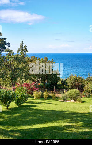 Idyllic summer view from a garden overlooking the Baltic Sea. In Lohme on the island of Rügen. - Stock Photo