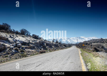 Long road stretch with snowcapped mountains in backdrop Crete Greece Europe - Stock Photo