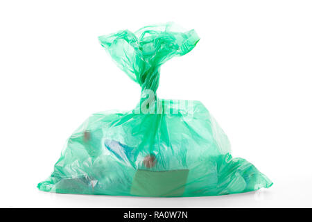 Green plastic bag with waste, isolated on white background, clipping path, excluding shadows, included - Stock Photo