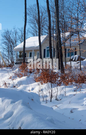 Snowy rural scene with Yellow house.  Winter scene in December in Quebec, Canada - Stock Photo