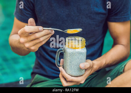 man eat dessert with chia seeds and mangoes by the pool in the morning. healthy eating, vegetarian food, diet and people concept - Stock Photo