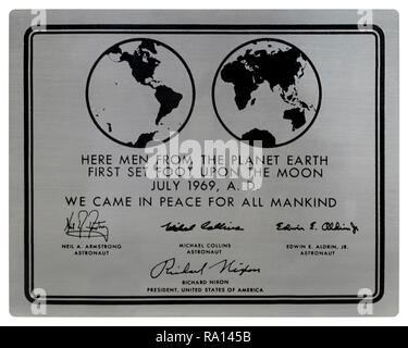 """An Apollo 11 stainless steel plaque as attached to the Apollo Lunar Modules that landed on the moon. Designed by Jack Kinzler, NASA the text reads: """"Here Men From The Planet Earth First Set Foot Upon The Moon, July, 1969, AD. We Came In Peace For All Mankind' followed by the engraved signatures of bears the signatures of Neil Armstrong, Michael Collins, Buzz Aldrin, and President Richard Nixon. The plaques of all the successful missions that landed remain on the moon. - Stock Photo"""