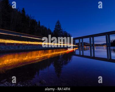Light trails column of people carrying hand-held torches along Bajer lake Fuzine in Croatia - Stock Photo