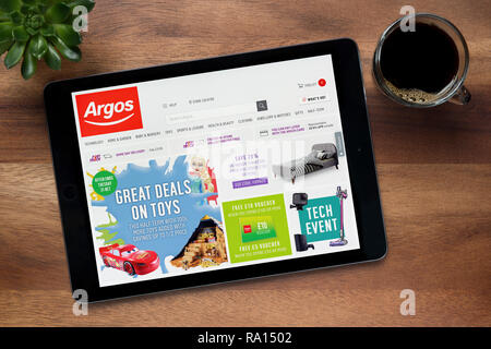 The website of Argos is seen on an iPad tablet, on a wooden table along with an espresso coffee and a house plant (Editorial use only). - Stock Photo