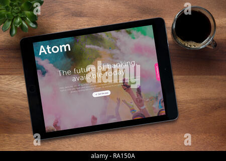 The website of Atom Bank is seen on an iPad tablet, on a wooden table along with an espresso coffee and a house plant (Editorial use only). - Stock Photo
